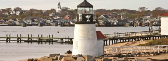Lighthouse near a pier and water in the fall