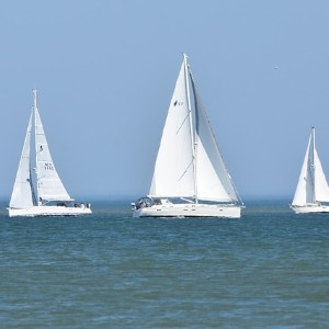 Three large all white sailboats together on crystal waters with a bright blue sky