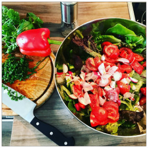 A bowl of bright green salad and vegetables in a bowl and a cutting board with a knife and a green pepper