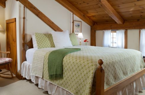Bedroom with wooden bed, white linens, white and green bedspread, and wooden rocking chair