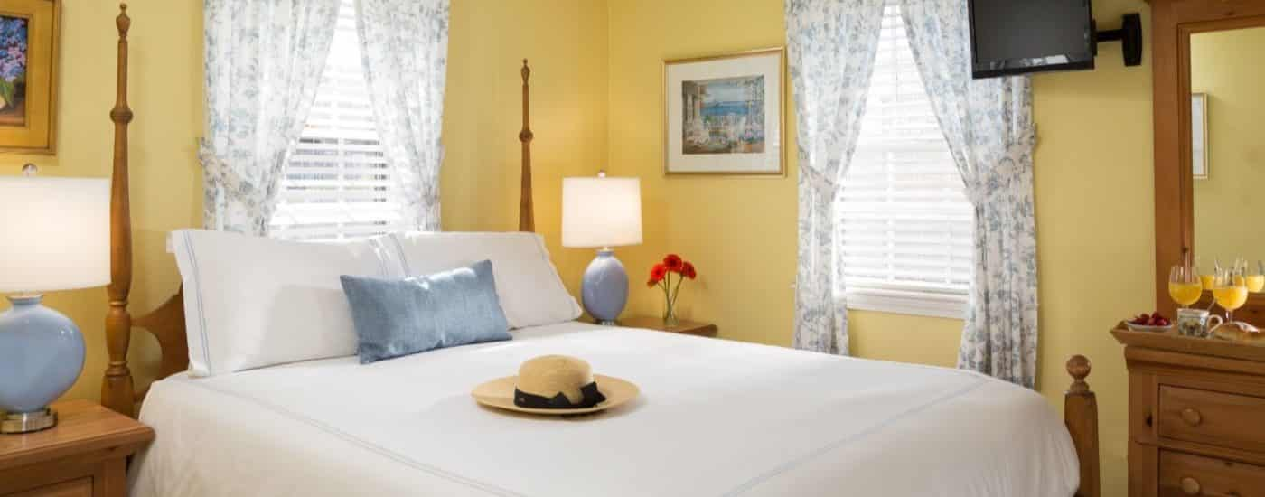Bedroom with yellow walls, light wooden bed and dresser, white bedding, and flat-screen TV