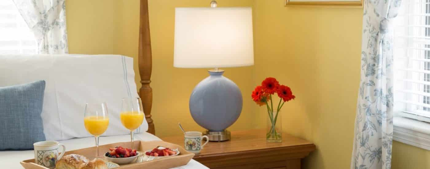 Bedroom with yellow walls, blue lamp with white shade on a light wooden nightstand, and tray full of pastries, fruit, juice, and coffee on top of the bed