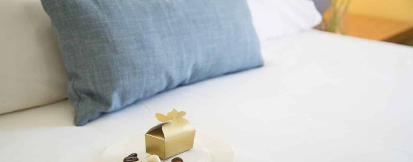 White plate full of chocolate candies and a gold box sitting on top of a bed with white bedding and blue denim pillow