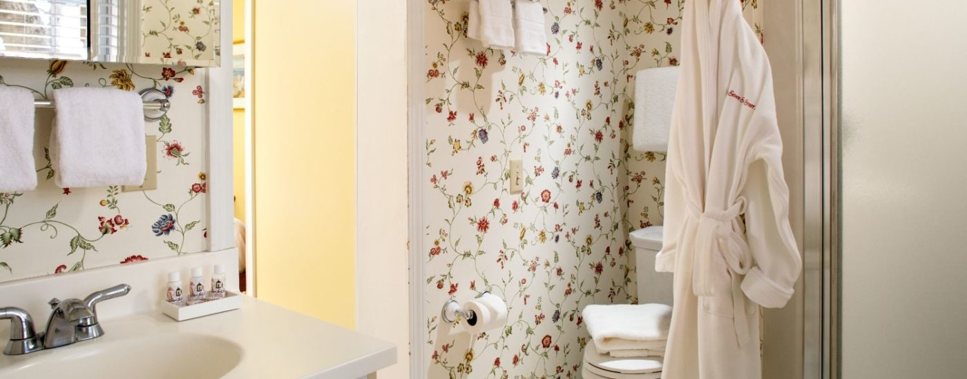 Bathroom with multicolored floral wall paper, white wooden vanity, stand up shower, and hanging white robe