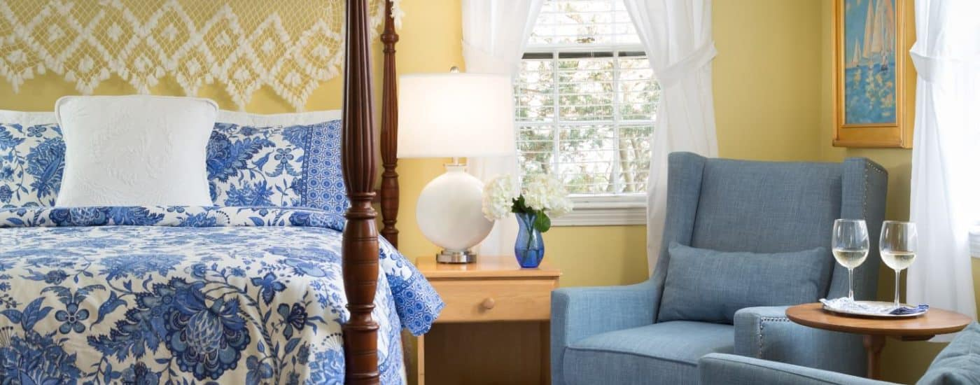Bedroom with yellow walls, dark wooden four-poster bed, blue and white paisley bedding, denim upholstered arm chairs