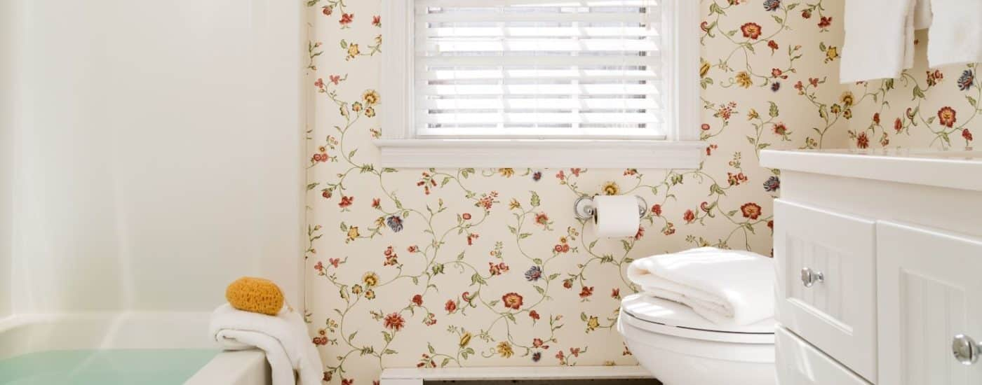 Bathroom with multicolored floral wall paper, white tile flooring, white wooden vanity, tub, and shower