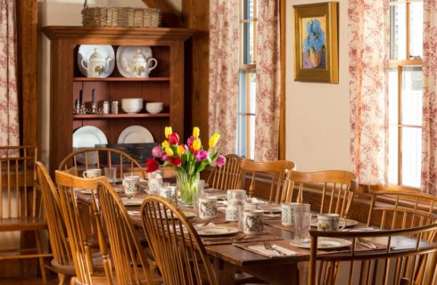 Dining room with a dark wooden china hutch and large wooden table and chairs with red, yellow and purple tulips in a vase on top