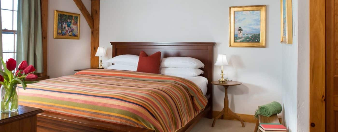 Bedroom with dark wooden headboard, white linens, multicolored striped bedspread, and wooden side tables with lamps
