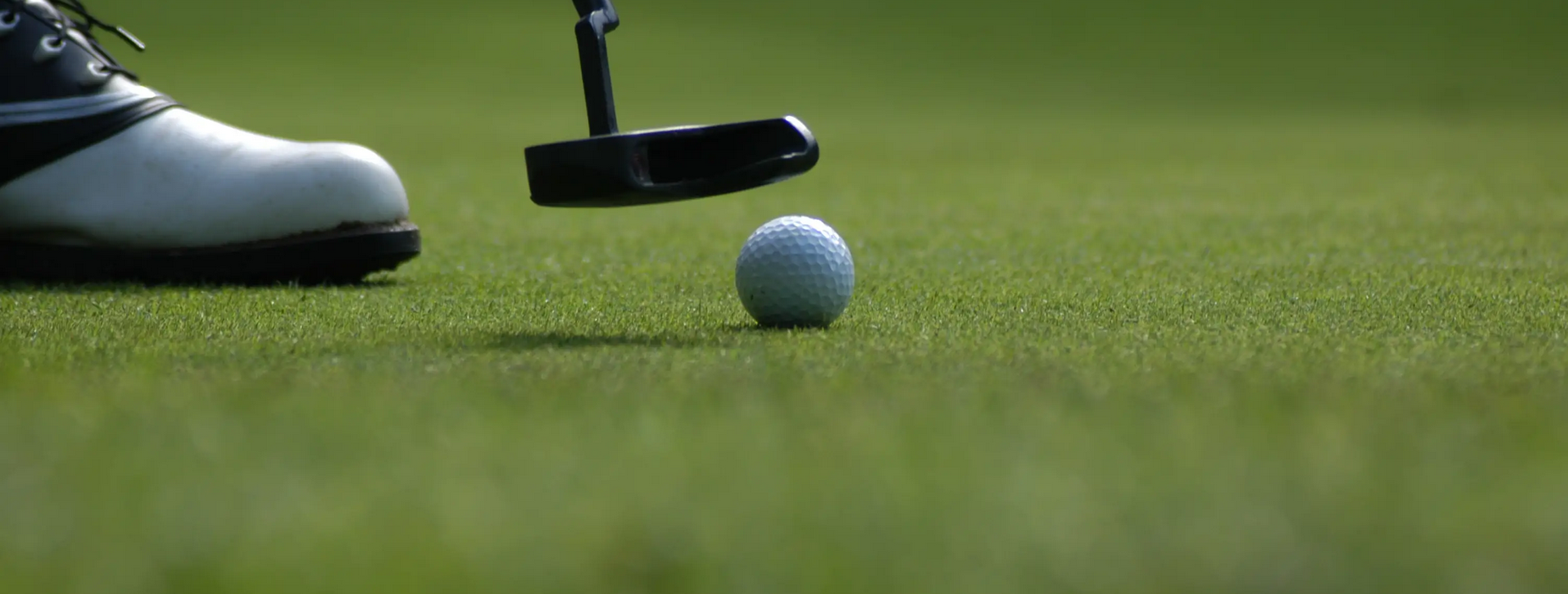 View of golfer's foot and club preparing to hit a ball