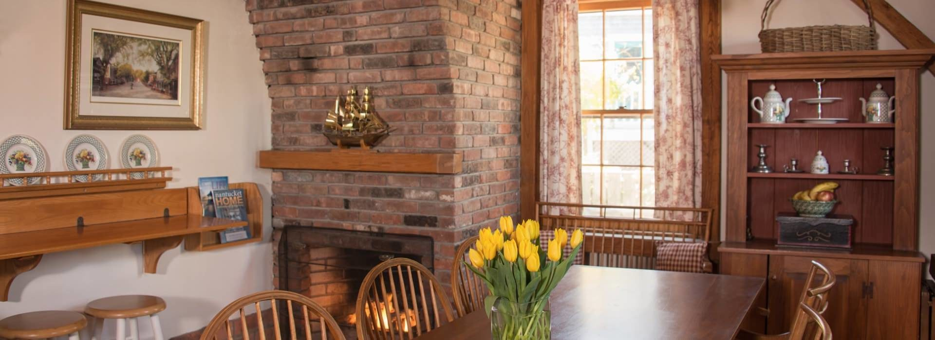 Dining room with large brick fireplace and large wooden table and chairs with yellow tulips in a vase on top