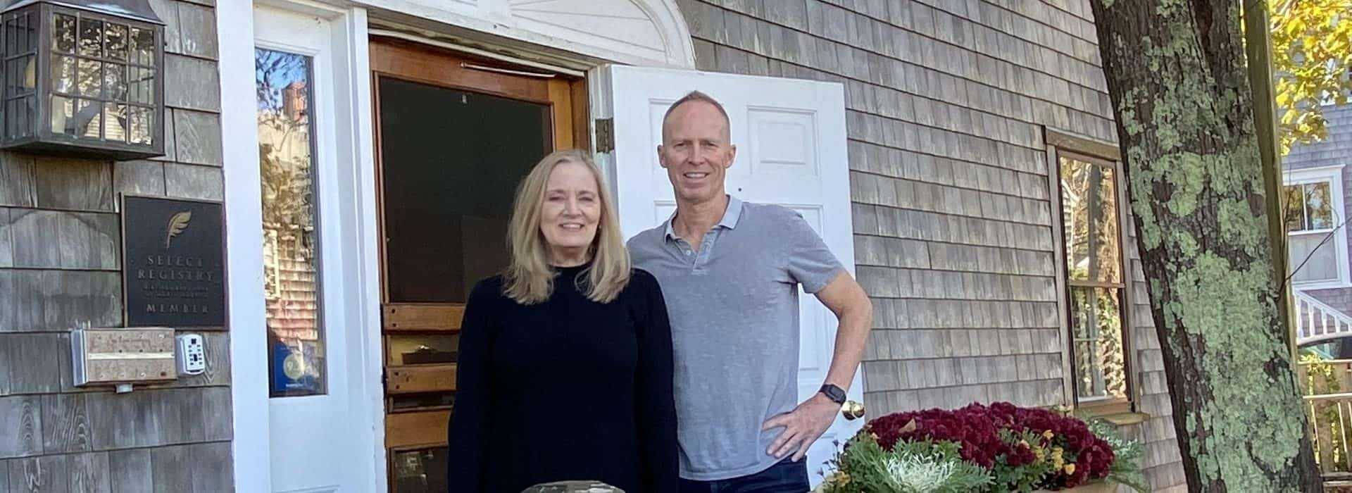 Lady with navy top and man with gray polo standing at the front entrance of the property