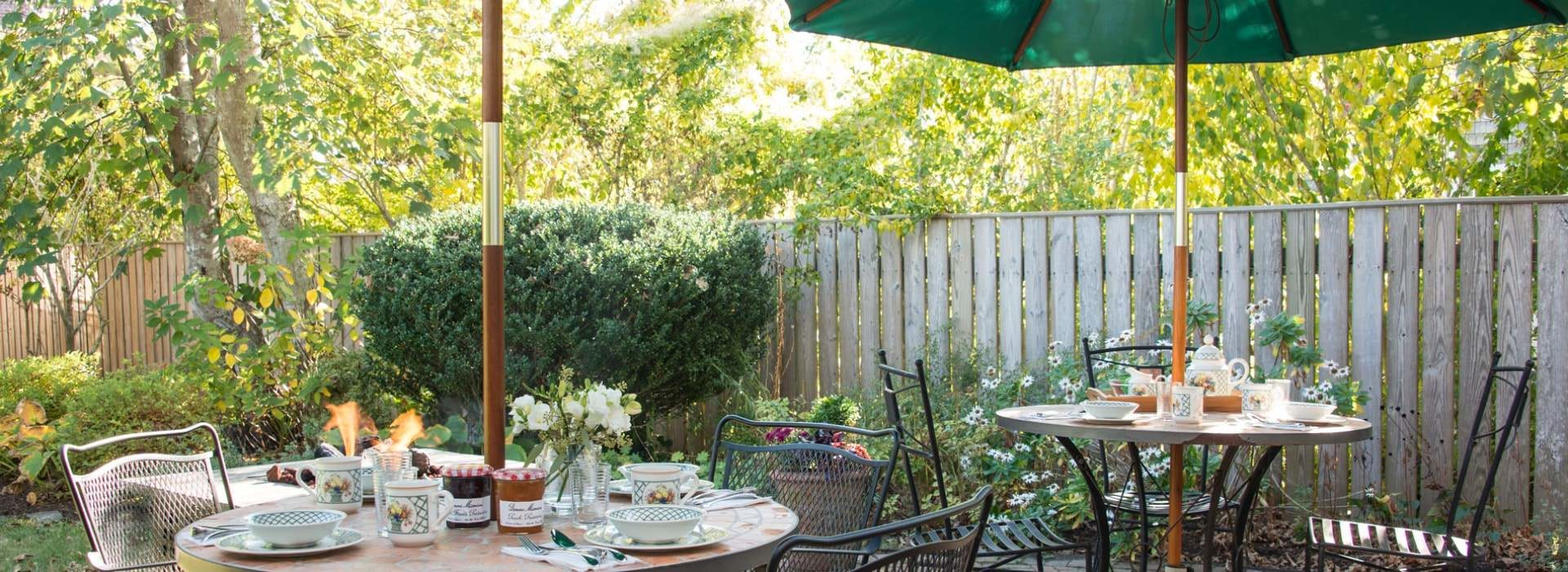 Two patio tables with opened umbrellas and place settings on a patio with green shrubs, trees, and flowers