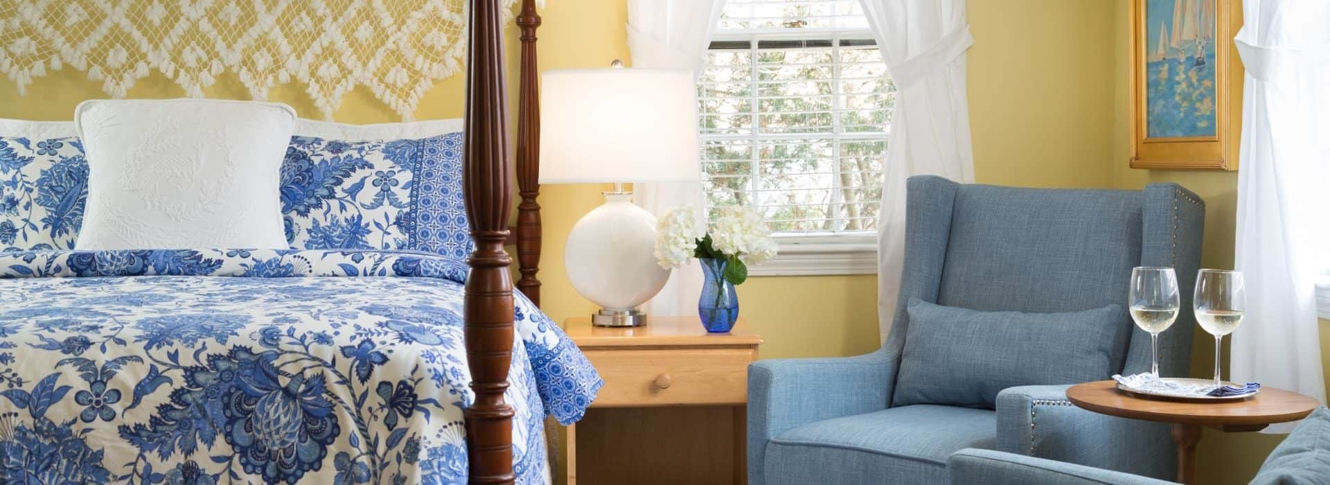 Bedroom with yellow walls, dark wooden four-poster bed, blue and white paisley bedding, denim upholstered arm chair