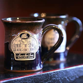 Dark colored stoneware mug with Seven Sea Street Inn logo on the front