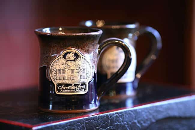 Dark colored stoneware mug with Seven Sea Street Inn logo on the front