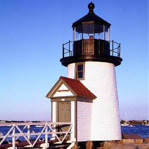 Tall white lighthouse with black lookout tower standing by waters edge