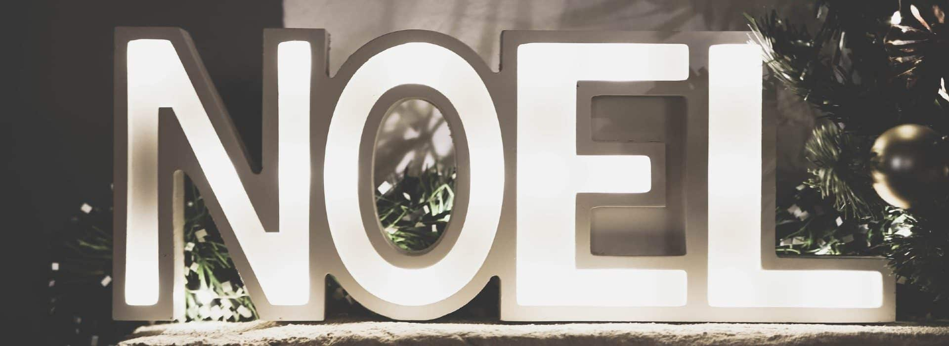 Black and white tone with the letters noel lit up with christmas tree branches behind