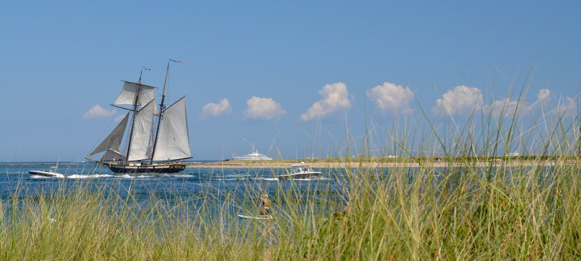 Body of water with beach in the background and large sailing ship, speedboat and paddleboarder in the water