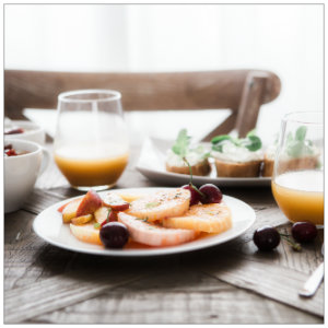 Table with breakfast food - plate of fruit and orange juice - image by brooke-lark-96402 www.unsplash.com
