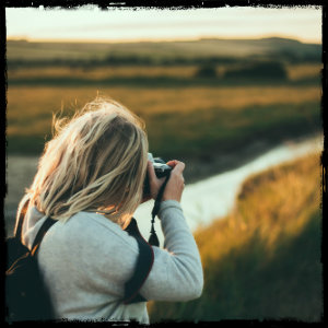 Blonde woman outdoors taking a picture of a field landscape - image by joseph pearson unsplash.com