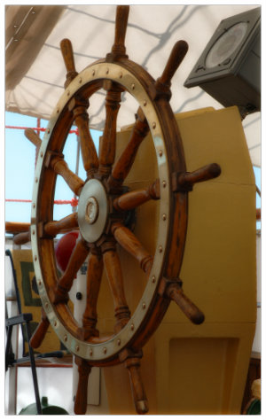 The wooden wheel of a sail boat