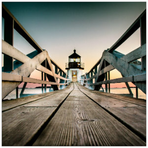 White lighthouse at the end of a long wooden boardwalk at dusk