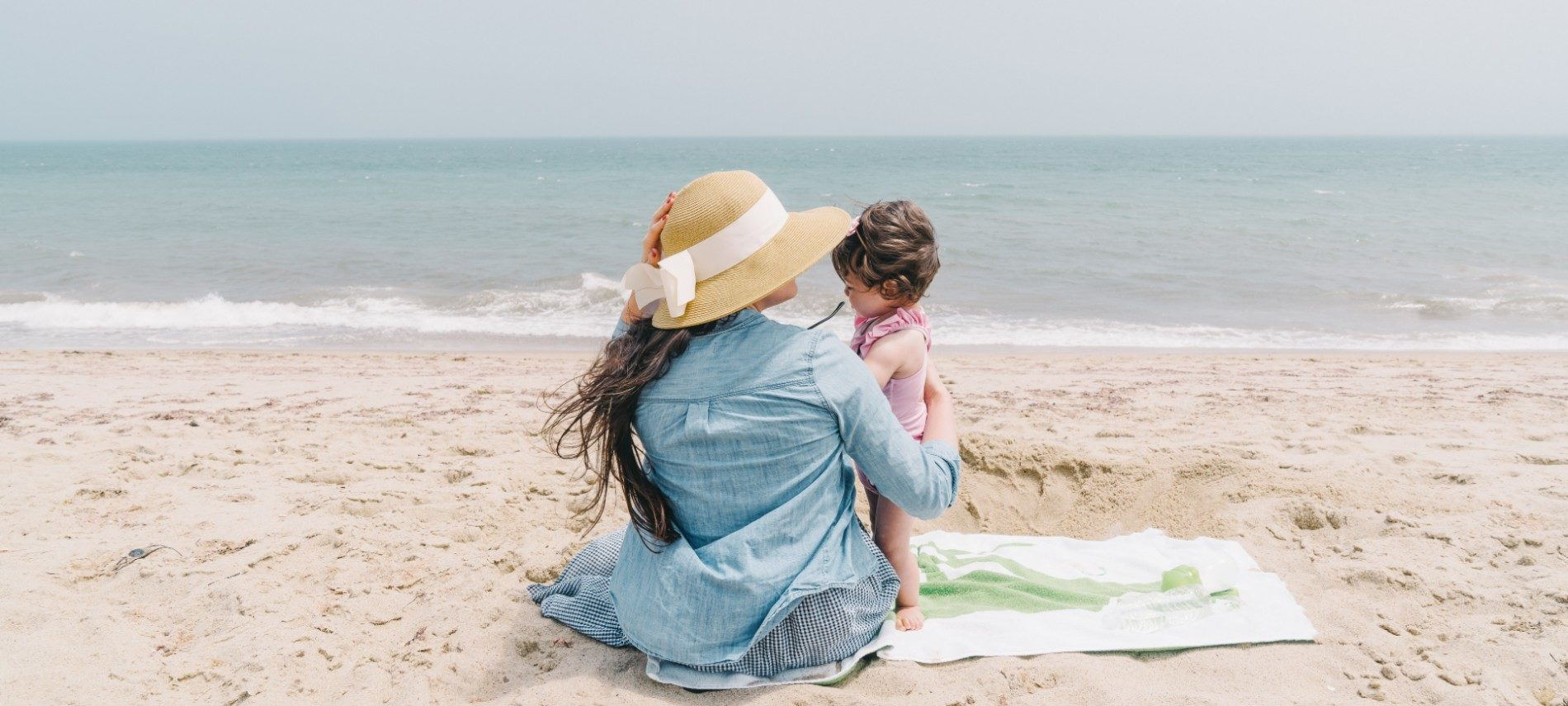 A woman in a blue shirt and hat with white ribbon sits on a beach with a young toddler at her side